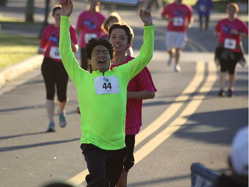 Runners crossing the finish line in the 2014 Sanford Riverwalk 5K